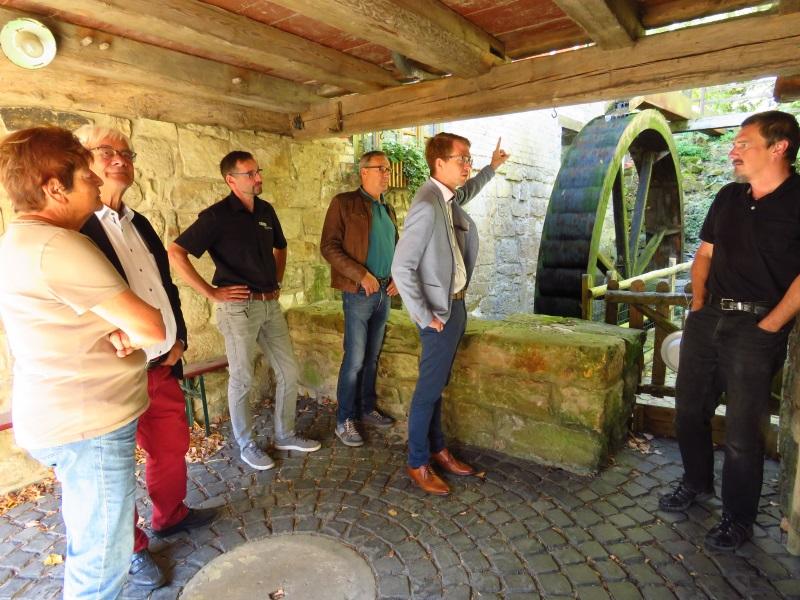 Michael Ruhl (2.v.r.) mit dem Bauherrn Stefan Müller (re.) vor dem historischen Mühlrad sowie Architekt Gans (2.v.l.) und Annerose Seipp, Kai Widauer und Norbert Reinhardt (v.l.)